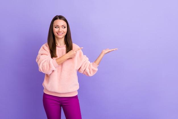 Foto de senhora engraçada segurando produto novidade com o braço aberto indicando dedo