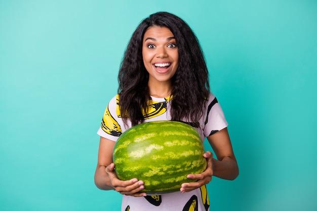 Foto de senhora negra segurando melancia olhar câmera sorriso brilhante usar camiseta com estampa de banana isolada cor turquesa de fundo