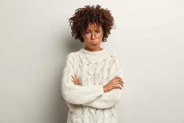 Foto de senhora ofendida com expressão facial rabugenta, lábios dobrados, mantém os braços cruzados sobre o peito, insatisfeita com comentários ruins, usa óculos redondos, suéter branco, está de mau humor.