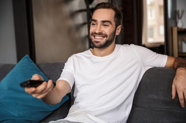 Foto de solteirão caucasiano dos 30 anos vestindo uma camiseta casual segurando o controle remoto enquanto está sentado no sofá na sala de estar
