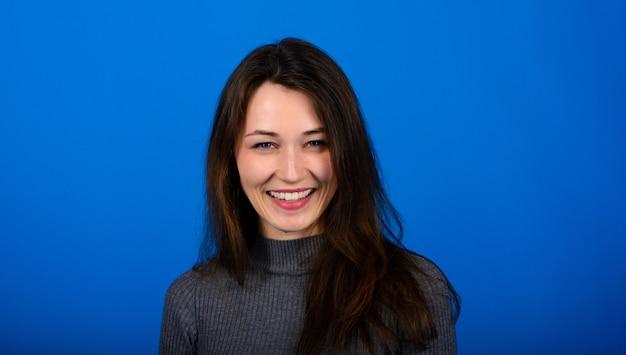 Foto de sorrindo, fêmea jovem alegre em vestido cinza