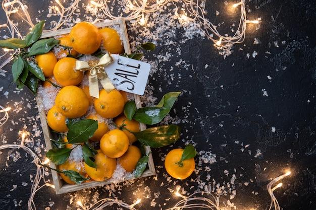 Foto de tangerinas em caixa de madeira, cartão postal na mesa preta com guirlanda