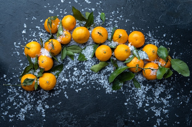 Foto de tangerinas na mesa preta com neve