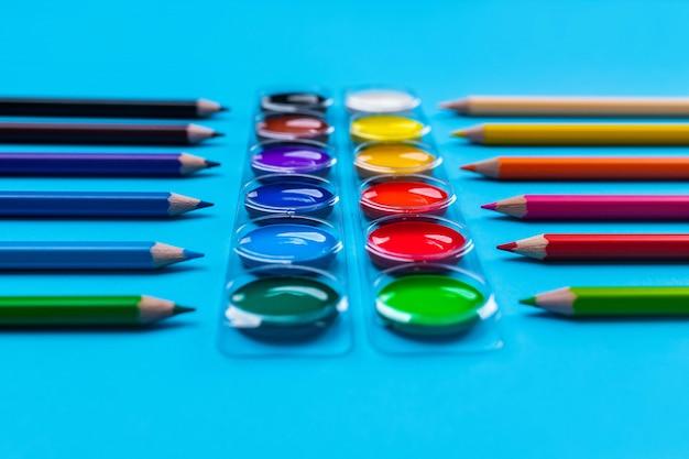 Foto de tintas guache coloridas brilhantes para desenho localizado no centro em um azul espalhado a lápis coloridos dispostos verticalmente. vista lateral. fechar-se.