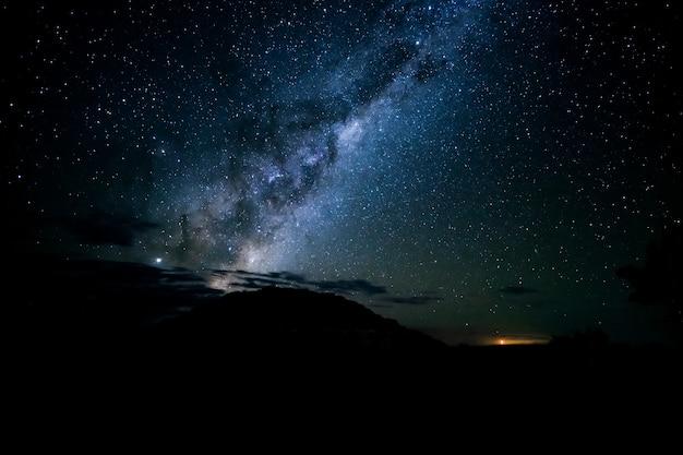 Foto de tirar o fôlego das silhuetas de colinas sob um céu estrelado à noite