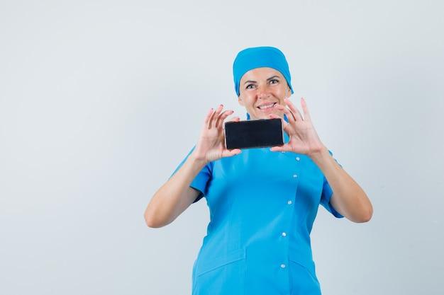 Foto de tomada de médica no celular em uniforme azul e parecendo se divertir. vista frontal.