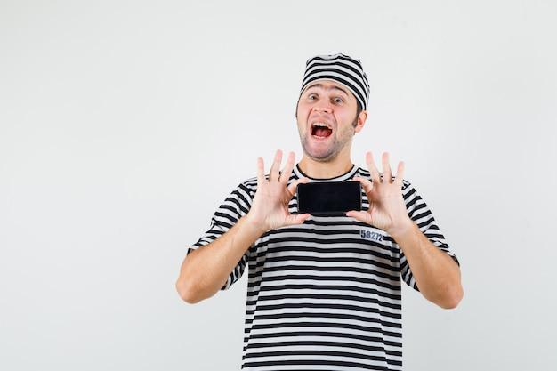 Foto de tomada jovem macho no celular em t-shirt, chapéu e olhando feliz, vista frontal.