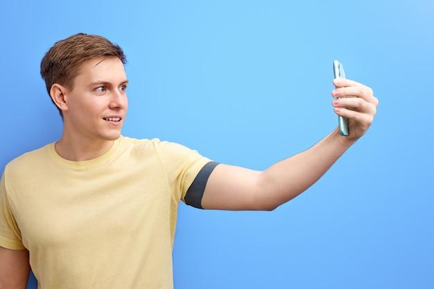 Foto de tomada masculina no smartphone, olhando para a câmera do telefone e sorrindo, isolada sobre fundo azul. retrato de estúdio