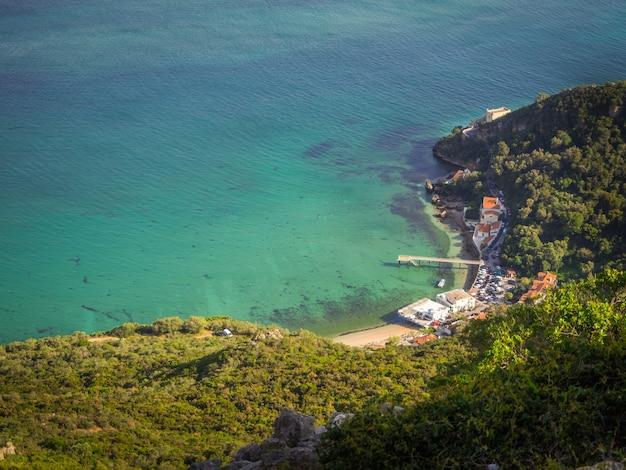 Foto de topo de um pequeno porto próximo a uma floresta no portinho da arrábida