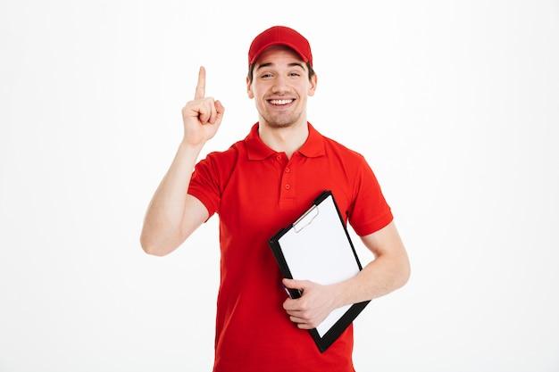 Foto de trabalhador de entrega atraente em t-shirt vermelha e boné, sorrindo e apontando o dedo no texto ou produto copyspace, mantendo a área de transferência, isolada sobre o espaço em branco