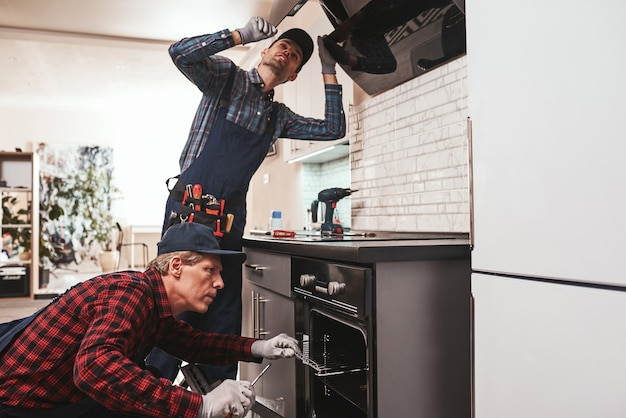 Foto de trabalho de colaboração de dois mecânicos trabalhando na cozinha