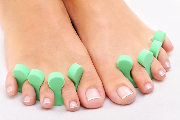 Foto de tratamento de beleza de pés bonitos aplicando pedicure