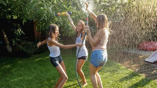 Foto de três adolescentes alegres dançando no jardim do quintal mangueira de água do jardim do útero