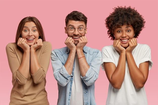 Foto de três amigos multiétnicos segurando queixos