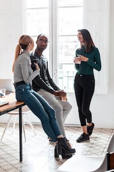 Foto de três jovens empresários tomando café enquanto faziam uma pausa no escritório.