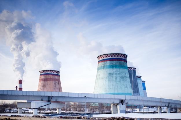 Foto de tubulações com fumaça, ponte, central elétrica