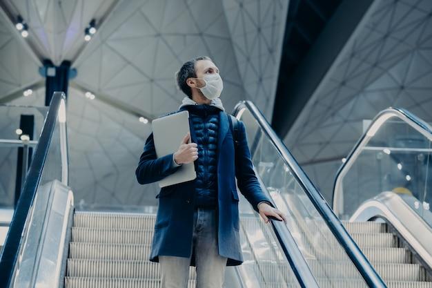 Foto de turista homem posa na escada rolante no aeroporto, chega em casa do exterior durante o surto de vírus, usa máscara protetora médica. passageiro evacuado. doença infecciosa. conceito de segurança pública