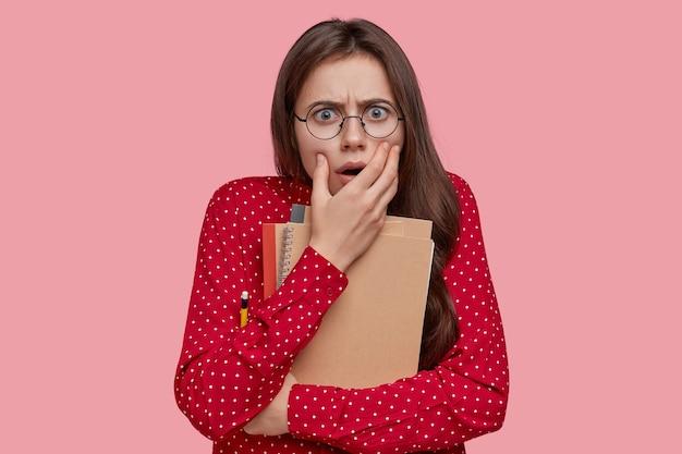 Foto de um adolescente assustado franzindo a testa, usa óculos ópticos, segura o bloco de notas com lápis, vestido com uma camisa vermelha, modelos sobre a parede rosa do estúdio