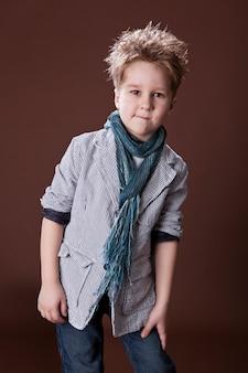 Foto de um adorável menino feliz vestindo uma camisa e olhando para a câmera no fundo marrom