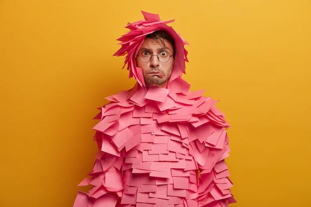 Foto de um anunciante masculino nervoso e constrangido morde os lábios, sente-se insatisfeito e cansado, coberto com notas adesivas cor-de-rosa sobre o corpo, posa dentro de casa contra uma parede amarela, tem expressão intrigada