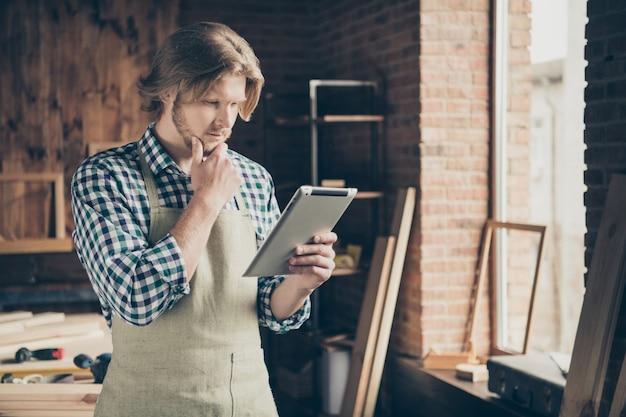 Foto de um artesão barbudo posando em sua marcenaria com um tablet