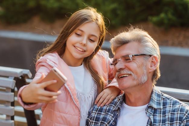 Foto de um avô e uma neta sentados em um banco conversando on-line pelo smartphone