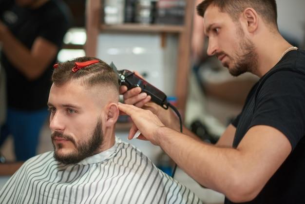 Foto de um barbeiro profissional no trabalho. jovem bonito cortando o cabelo na barbearia local.