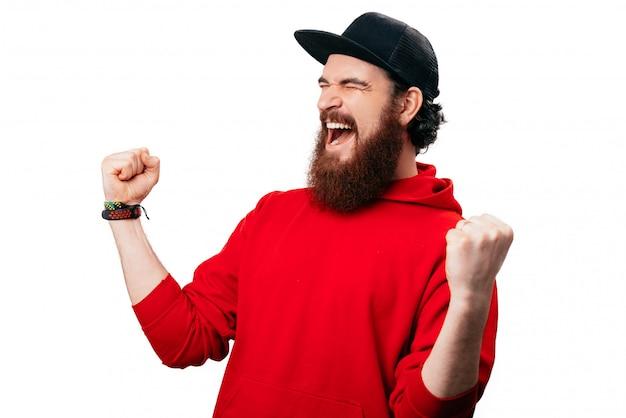 Foto de um barbudo animado, comemorando com os braços erguidos e os olhos fechados na whit