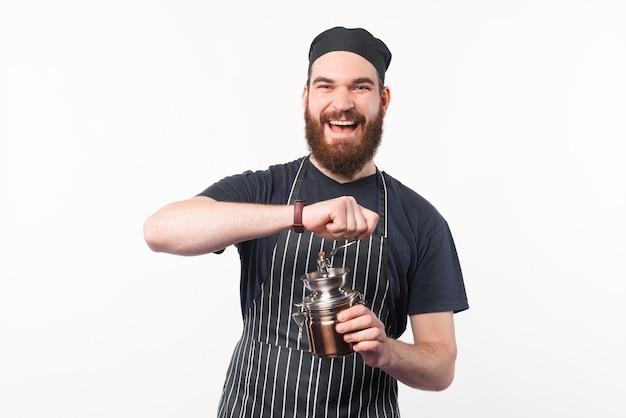 Foto de um barista sorridente moendo alguns grãos de café com um moedor de café