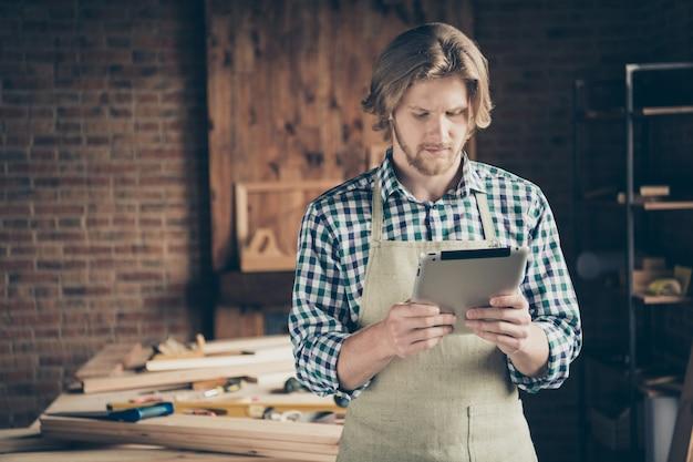 Foto de um belo artesão barbudo posando em sua marcenaria com um tablet