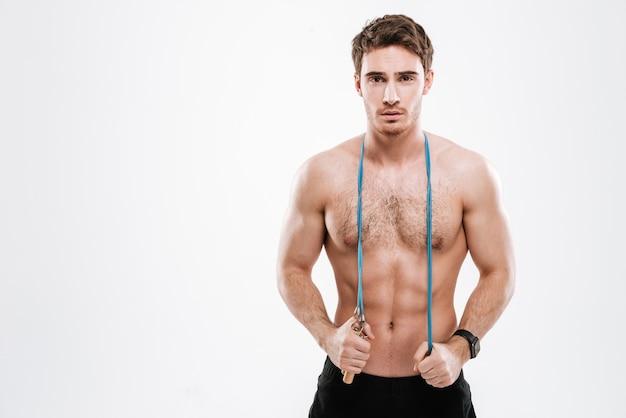 Foto de um belo atleta em pé com pular corda na parede branca.