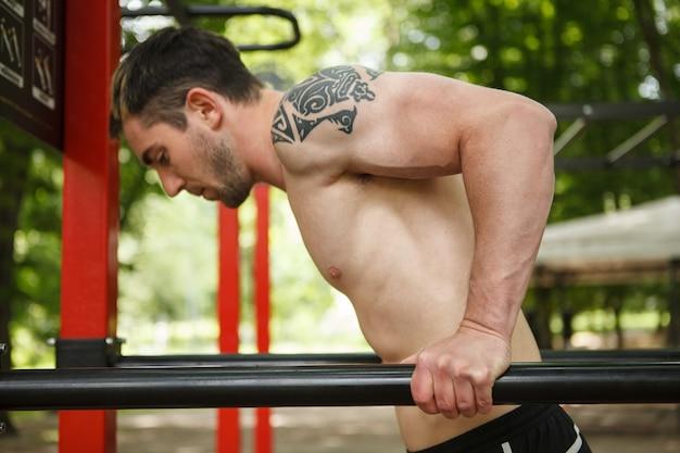 Foto de um belo esportista fazendo exercícios de tríceps no parquinho de ginástica