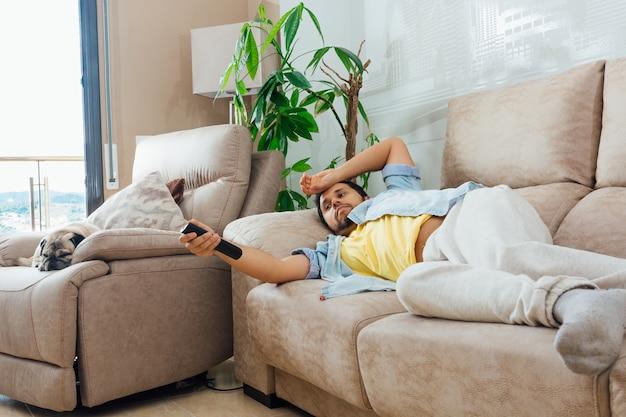Foto de um belo homem hispânico deitado em um sofá e assistindo tv