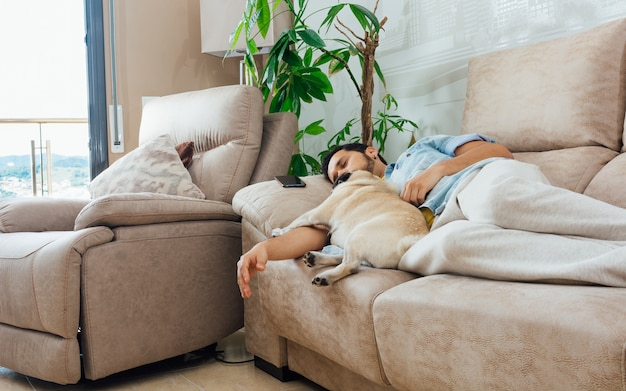 Foto de um belo homem hispânico dormindo em um sofá com seu cachorro