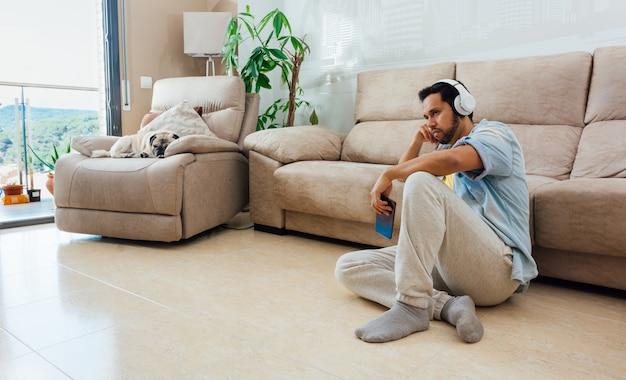 Foto de um belo homem hispânico sentado em um sofá e assistindo tv
