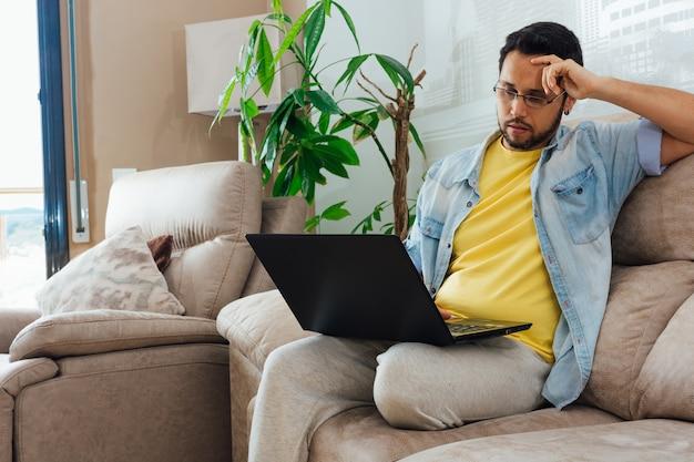 Foto de um belo homem hispânico sentado em um sofá e usando um laptop