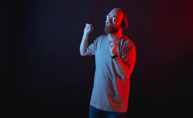Foto de um belo jovem barbudo homem moderno ouvindo música e dançando na parede escura com luzes de néon vermelhas e azuis