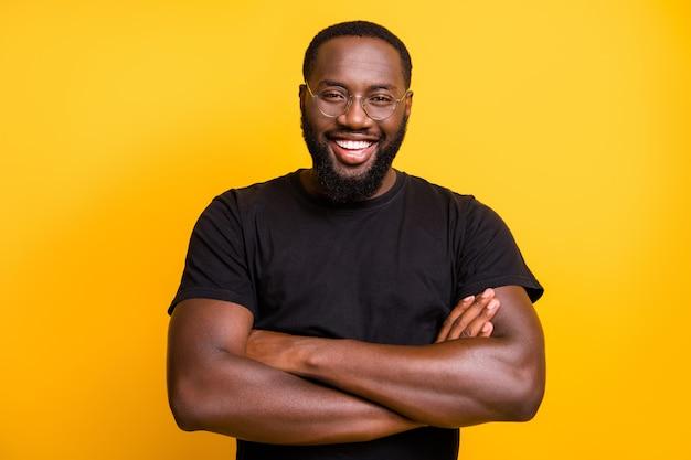 Foto de um cara alegre, cheio de dentes e sorrindo, com os braços cruzados, de pé, isolado com segurança em uma camiseta sobre uma parede de cor vibrante