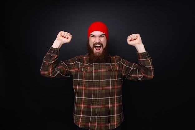 Foto de um cara barbudo com camisa e chapéu vermelho, gritando e comemorando com os braços levantados sobre uma parede escura