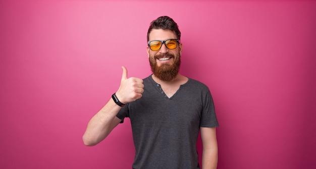 Foto de um cara barbudo mostrando o polegar em pé sobre um fundo rosa isolado