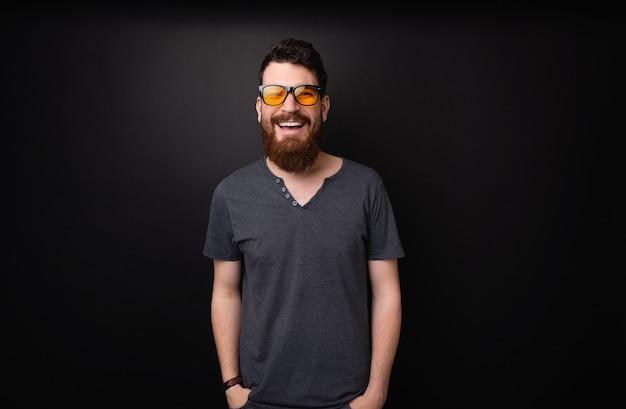Foto de um cara barbudo usando óculos escuros elegantes, sorrindo para a câmera sobre um fundo escuro
