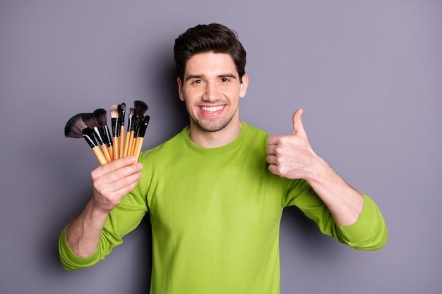 Foto de um cara bonito do trabalhador com escovas mestras de rosto novo levantando o polegar para cima aconselhando acordo expresso de boa qualidade usar suéter casual verde isolado parede cor cinza