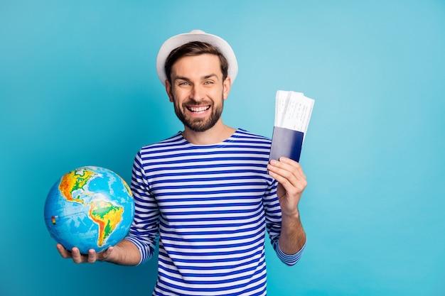 Foto de um cara bonito e alegre segurar mundo globo viciado viajante show ingressos esperar vôo check-in vestir camisa listrada de marinheiro colete vestido panamá isolado cor azul