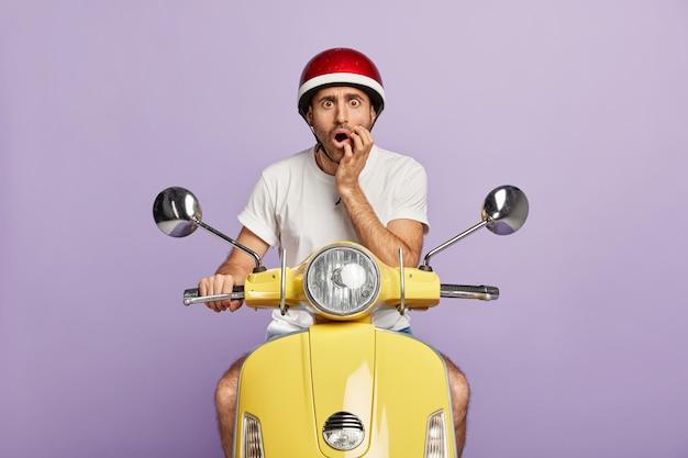 Foto de um cara chocado com um capacete dirigindo uma scooter amarela