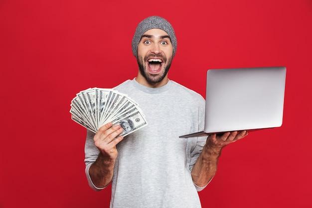 Foto de um cara de 30 anos surpreso com roupas casuais segurando dinheiro e um laptop prateado isolado