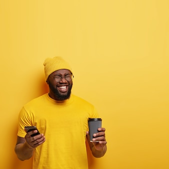 Foto de um cara de pele escura feliz e satisfeito fecha os olhos de prazer, usa um chapéu e uma camiseta amarelos elegantes, mensagens em redes sociais, segura celular moderno e café para viagem, ri de algo engraçado