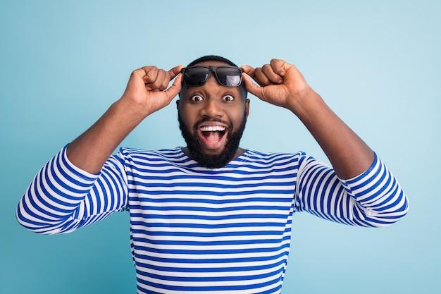 Foto de um cara de pele morena atraente, boca aberta, ver ler, assistir a temporada de vendas, abrir anúncio banner usar óculos de sol camiseta listrada de marinheiro colete parede azul
