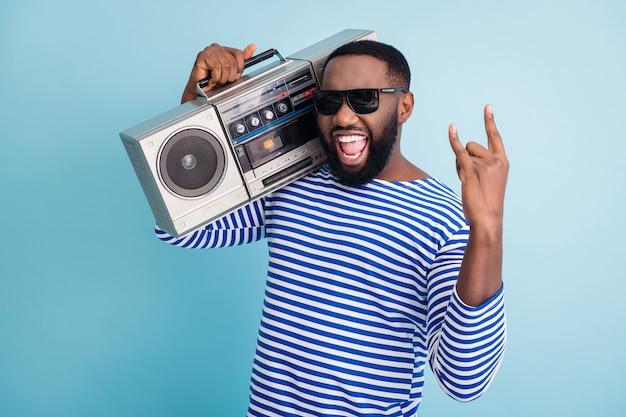 Foto de um cara engraçado segurando um gravador retrô com símbolo de chifres