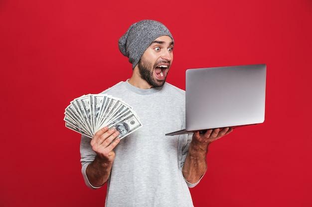 Foto de um cara estiloso de 30 anos em roupas casuais segurando dinheiro e um laptop prateado isolado