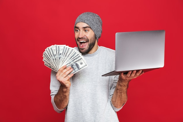 Foto de um cara feliz dos 30 anos em roupas casuais segurando dinheiro e um laptop prateado isolado